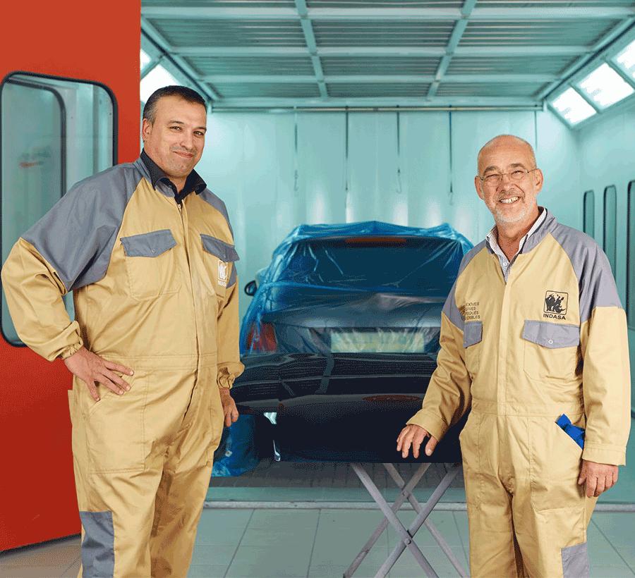 dois pintores à frente de cabine de repintura com carro no interior